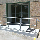 New entry - cut into existing wall panels, form new opening and entry doors, new ramp and railing to BCA standards